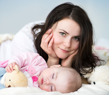 baby bed: Young mother with her sleeping  baby  in bed