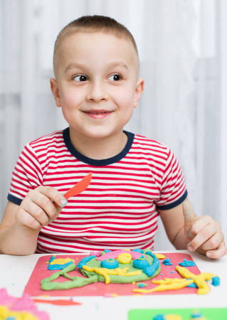 little dough: Little Boy Playing with Color Dough Stock Photo