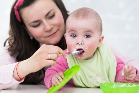 Mother feeding baby with spoon Фото со стока