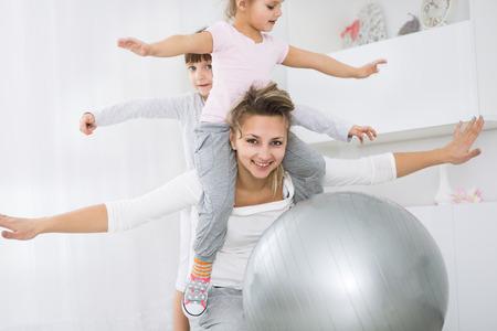 gymnastics: Mutter mit Töchtern tun Gymnastik-Übungen mit Bällen
