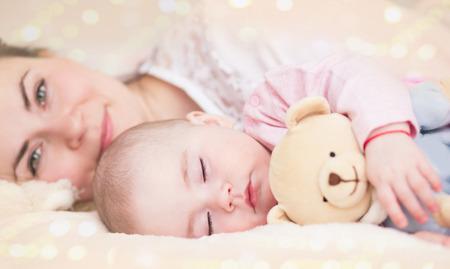 cama: Parenthood. Motherhood.Young madre y su beb�, durmiendo en la cama Foto de archivo
