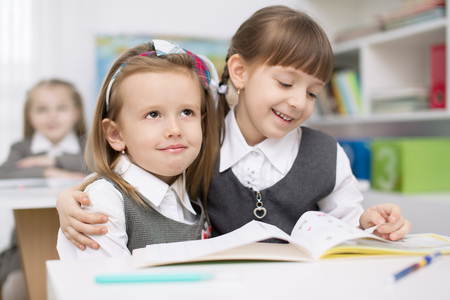 school uniforms: Portrait of two little girls looking at camera at workplace with children on background Stock Photo