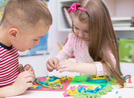 niños jugando: Niños que juegan con arcilla