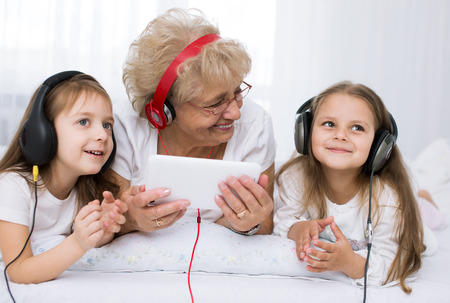 grandmother with granddaughters  listening for the music using headphones