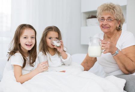 leche de soya: Hermosa abuela con leche de consumo nieta, el concepto de salud.