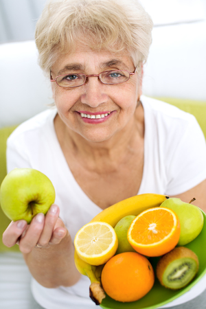 Portrait of a smiling senior woman holding a variety of fruits in her hands Фото со стока