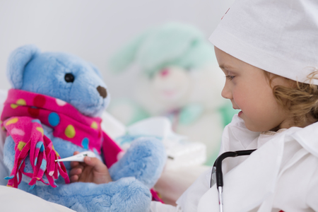 sick child: cute little girl dressed as doctor playing with toy
