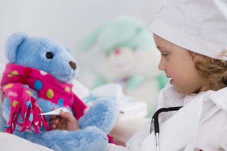 enfant malade: mignonne petite fille habillée comme médecin en jouant avec des jouets Banque d'images