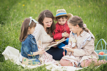 storytelling: Mother reading a book with children
