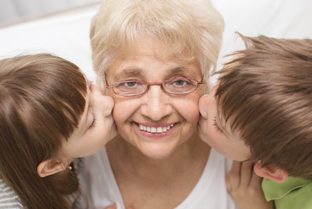 grandsons: portrait of a cute grandchildren kissing grandmother Stock Photo
