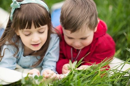 happy families: Two little kids having fun in summer park while laying on lawn Stock Photo