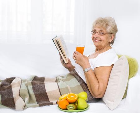 orange fruit: Senior woman reading book and relaxing in sofa