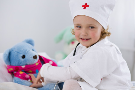 cute little girl dressed as doctor playing with toy