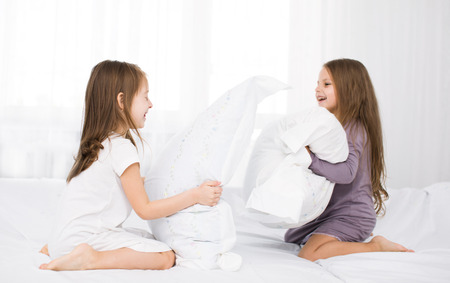 combate: Ni�os Retrato lucha con almohadas en la cama