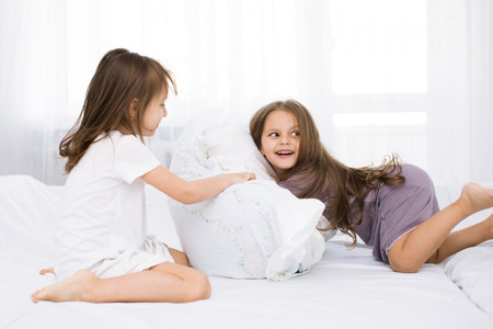 brother sister fight: Portrait kids fighting with pillows in bed