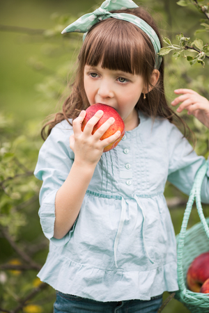 eating fruits: Summer portrait of a cute girl with apples
