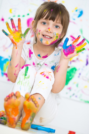 Portrait of a cute cheerful happy little girl showing her hands painted in bright color