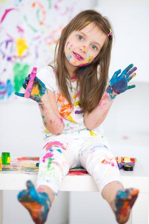 niñas pequeñas: Retrato de una niña alegre feliz lindo que muestra sus manos pintadas de color brillante Foto de archivo