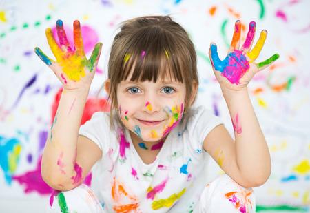 Retrato de una niña alegre feliz lindo que muestra sus manos pintadas de color brillante Foto de archivo - 41429239
