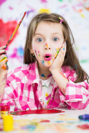 Portrait of a cute cheerful happy little girl showing her hands painted in bright color Фото со стока - 41429242