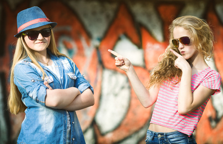 Having Fun: Portrait of happy teens having fun by painted wall Stock Photo