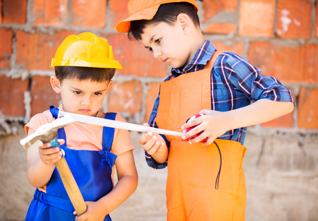 manual measuring instrument: little builders  in hardhats with measuring tape working outdoors
