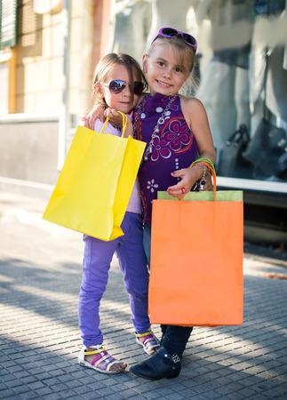 chicas de compras: dos niñas lindas con bolsas de compras en la ciudad
