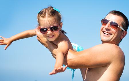 convivencia familiar: Padre con su hija jugando en la playa en el tiempo del día.