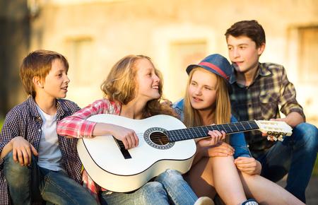cantando: Retrato de adolescentes felices jugando la guitarra rodeado de amigos