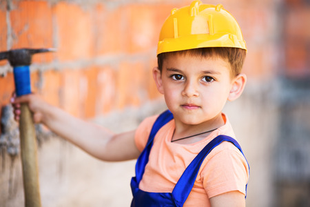 manual measuring instrument: cute little builder  in hardhats with hammer working outdoors Stock Photo
