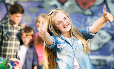 painted wall: Portrait of happy teens having fun by painted wall Stock Photo