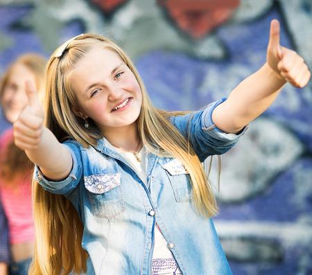 jovenes felices: Retrato de adolescentes felices que se divierten por la pared pintada