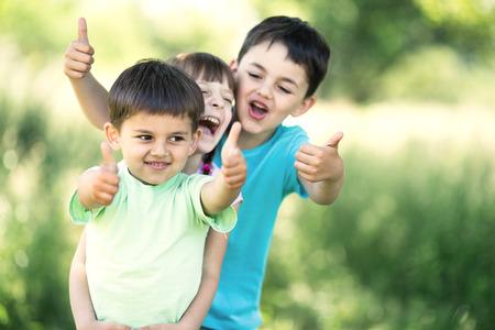preschooler: summer portrait of happy children together showing their thumbs up outdoors