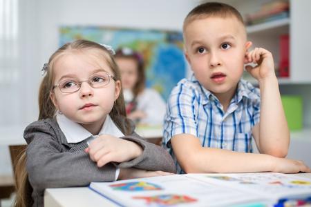 preschooler: Little schoolchildren are reading book at school