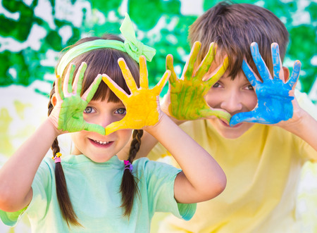 dirty girl: Playing with colors.  Beautiful children with colorful hands, creative child concept Stock Photo