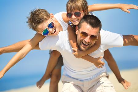 padres: Padre con los niños que se divierten en la playa en el tiempo del día.