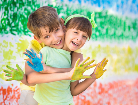 kids fun: Playing with colors.  Beautiful children with colorful hands, creative child concept Stock Photo