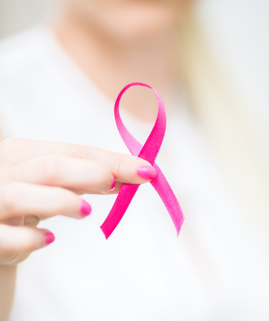 breast cancer awareness ribbon: woman holding pink breast cancer awareness ribbon