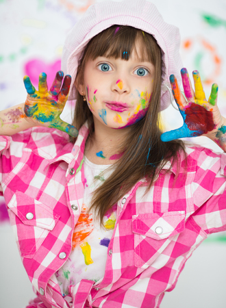 fun background: Portrait of a cute cheerful happy little girl showing her hands painted in bright colors Stock Photo