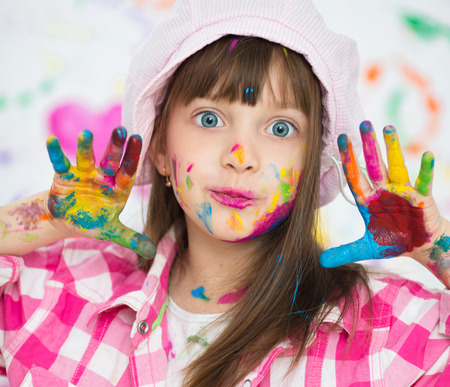arts: Portrait of a cute cheerful happy little girl showing her hands painted in bright colors Stock Photo