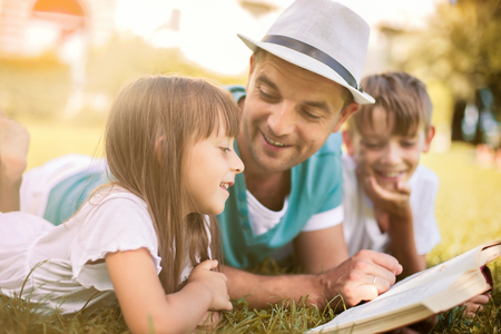 niños riendose: Padre leyendo un libro a sus hijos al tiempo que sienta al aire libre en la hierba en el parque Foto de archivo