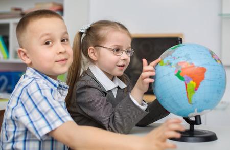 preschool children: little schoolchildren are examining globe