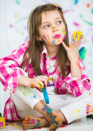 playschool: Portrait of a cute cheerful happy little girl showing her hands painted in bright colors Stock Photo
