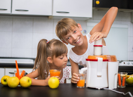 juice fresh vegetables: cute kids making carrot and apple juice with a juice extractor Stock Photo
