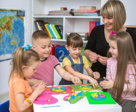 maestra preescolar: Niños felices con el maestro jugando con juego de colores de masa en el aula Foto de archivo