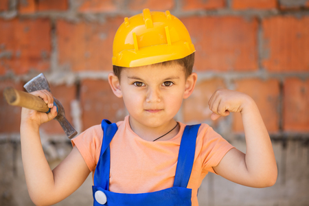 cute little builder in hardhats with hammer working outdoors