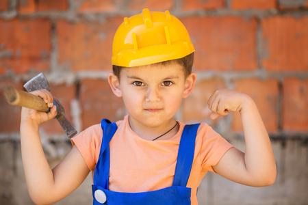 builder: Peque�o constructor lindo en cascos con martillo de trabajar al aire libre Foto de archivo