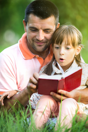family outside: Father is reading a book to his daughter  outdoors Stock Photo