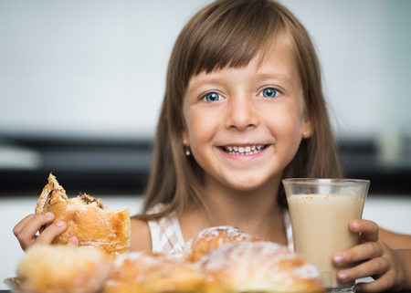 girl home: happy little girl having breakfast, coffee with croissants at home Stock Photo