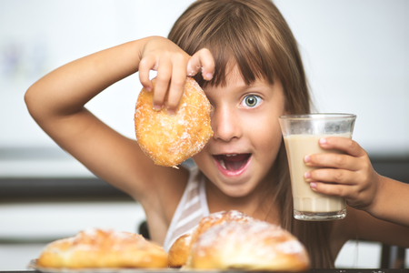 breakfast cup: happy little girl having breakfast, coffee with croissants at home Stock Photo